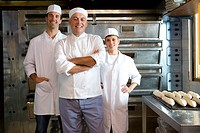 Bakers by tray of baguettes, smiling, portrait (thumbnail)