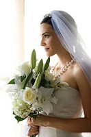 Profile portrait of Caucasian mid_adult bride holding flower bouquet.