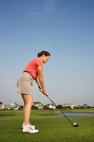 Caucasian mid_adult woman preparing to drive golf ball.