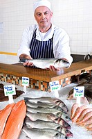 Fishmonger behind counter in shop, holding fish, portrait