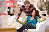 Young couple shopping, man smiling at woman on sofa (thumbnail)