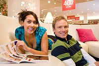Young woman with brochure on sofa in shop by man, smiling, portrait