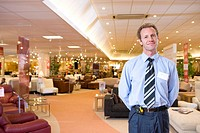 Salesman in furniture shop, smiling, portrait