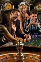 Men and women gambling at roulette table, smiling (thumbnail)