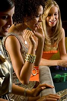 Young women gambling, smiling, side view