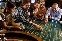Men and women gambling at roulette table in casino, elevated view (thumbnail)