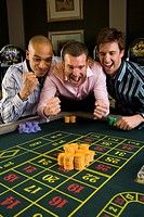 Young man with friends gambling at roulette table in casino, smiling (thumbnail)
