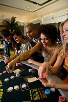 Young men and women gambling in casino, side view