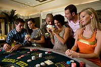 Young men and women gambling at poker table in casino, smiling (thumbnail)