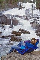 Hiker relaxes by Crazy Creek, near Yellowstone National Park.