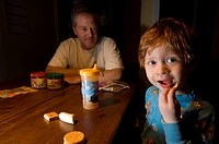 A 3_year_old boy shares a snack with his father.