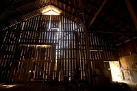 An old barn with light filtering through the boards.