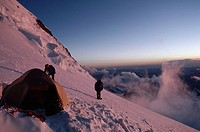 Climbers stand outside their tent at 20,000 feet on Mount Nun.