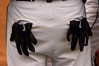 A man wearing baseball pants with gloves stuffed in the pockets.