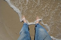 Waves splash against a man´s feet in Gulf Shores, AL.