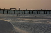 A person strolls on a pier.