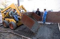 Men work to pour a concrete driveway.
