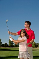 Golf instructor teaching young female student 13_14 putting on golf course