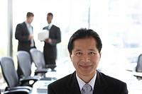 Senior businessman at head of boardroom table, portrait