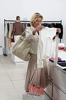 Woman in store, holding and looking at clothes