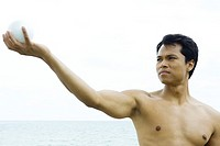 Man at the beach with arm raised, looking at ball in hand, close-up
