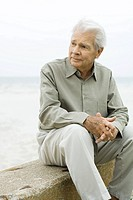 Senior man sitting near sea, looking away