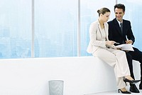 Male and female executives sitting on ledge by window, discussing document