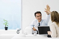 Business associates giving each other high-five in office