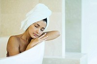 Woman sitting in bathtub with towel wrapped around hair, head resting on arms, eyes closed
