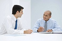 Two businessmen sitting at table having meeting