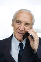 Senior businessman using cell phone, smiling, portrait