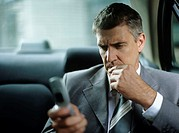 Business man sitting in car with hand on chin,using mobile phone
