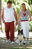 Mid adult couple in sportswear walking dog in park
