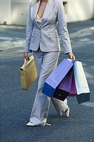 Young businesswoman walking with shopping bags and briefcase