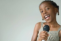 Little girl singing into microphone, smiling at camera, close-up