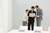 Three business associates standing in conference room, looking at laptop computer together