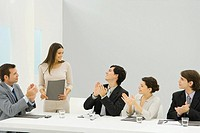 Businesswoman standing beside conference table, holding document, colleagues looking at her and clapping