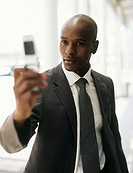 Businessman photographing self with camera phone