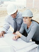 Man and woman in hard hats looking at blueprints on construction site