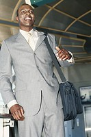 Businessman standing in airport with carrying bag, low angle view
