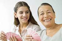 Senior woman and granddaughter playing cards