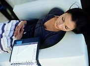 Mid adult woman lying down on sofa,open diary beside,high angle view