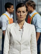 Business woman and two commercial dock workers in orange waistcoats,focus on foreground