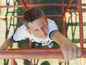 Boy 4_7 on climbing frame, smiling, elevated view