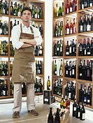 Man standing in front of wine bottle display, low angle view, portrait