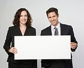 Portrait of young business man and woman with placard