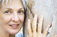 Senior woman leaning against tree trunk, smiling at camera, close-up