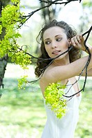 Young woman holding flowering tree branch, looking away