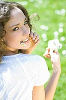 Young woman holding flower in mouth, looking over shoulder at camera (thumbnail)