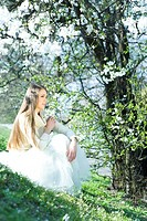 Teenage girl sitting outdoors, holding flowers, looking away (thumbnail)